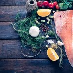 Raw salmon and large group of ingredients on wooden bacground with blank space,selective focus